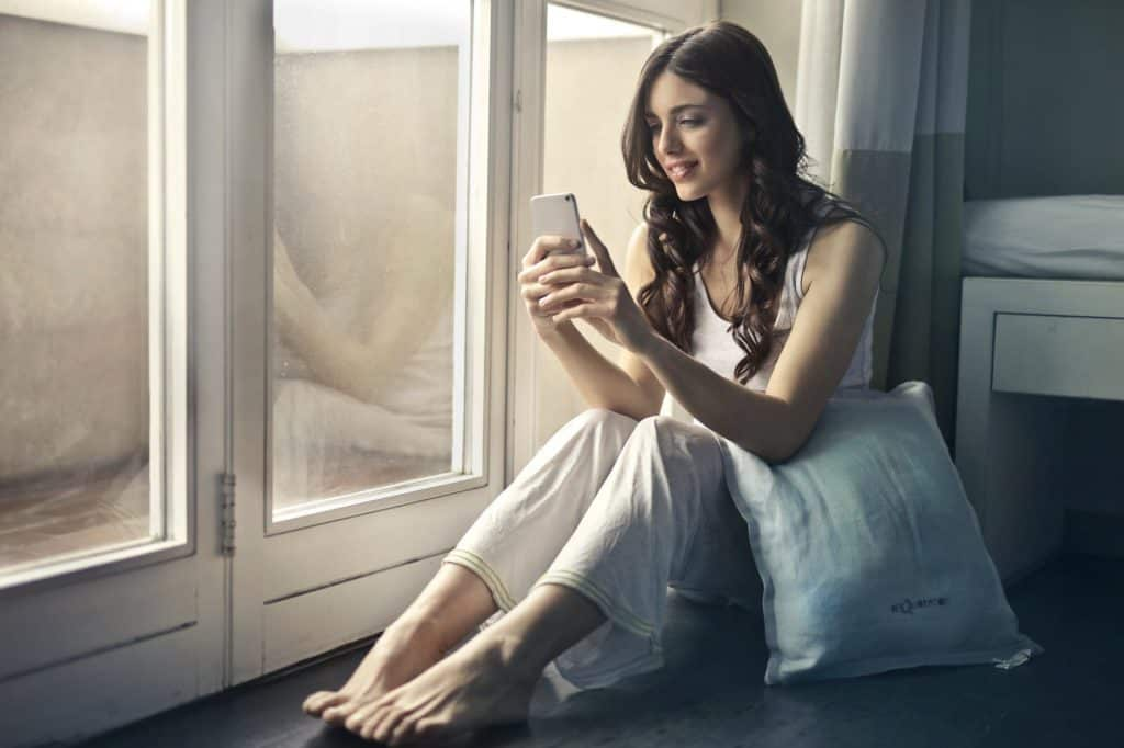 A girl confidently using her phone from her bedroom