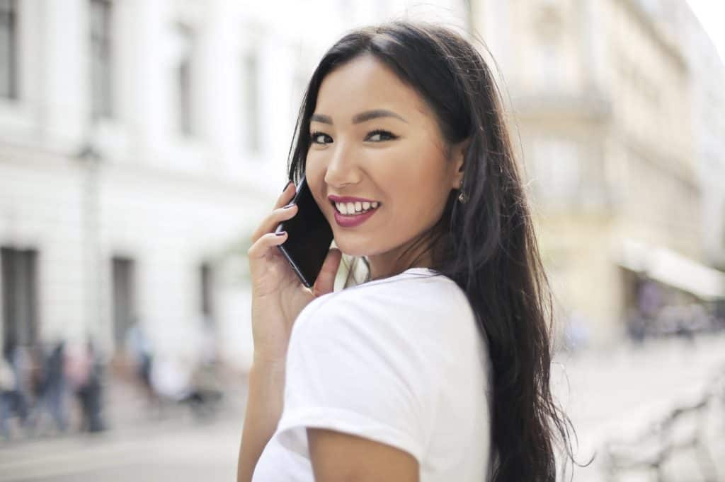 A pretty asian girl smiling on the phone