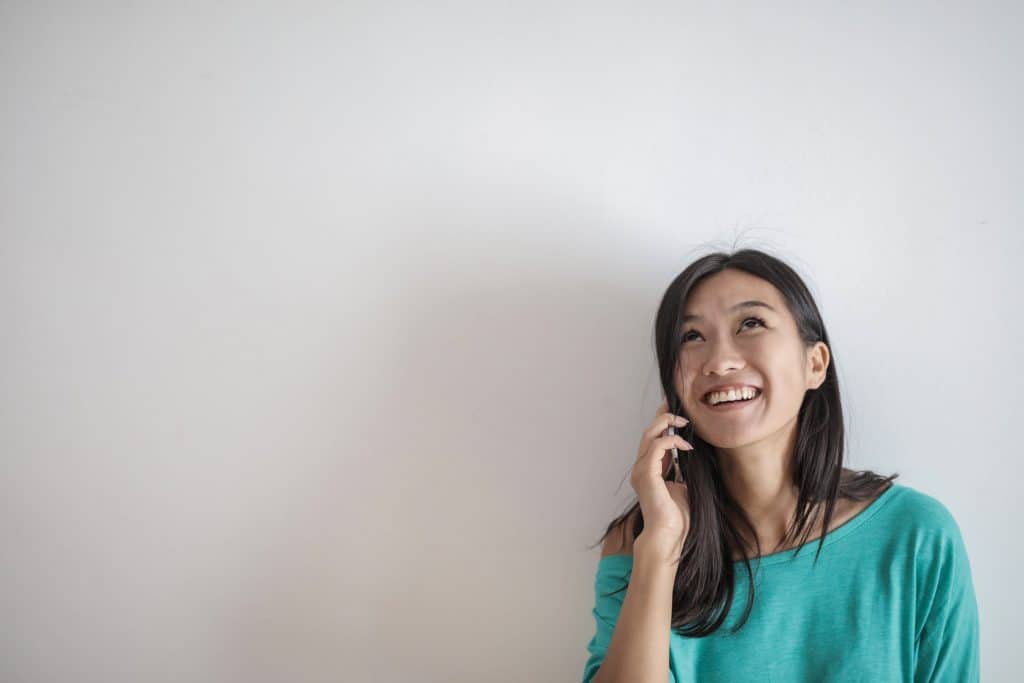 An Asian woman on the phone with a smile on her face