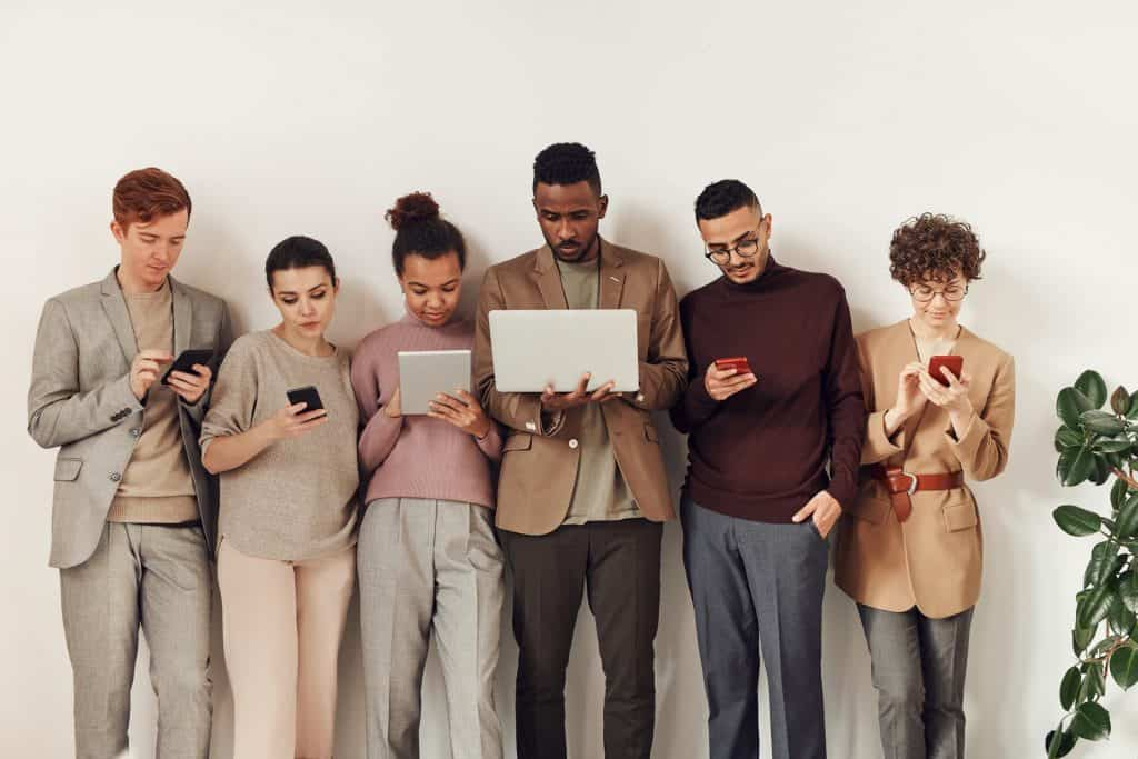 A group of people holding their phones and laptops