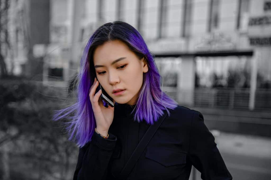 A girl with purple hair on the phone
