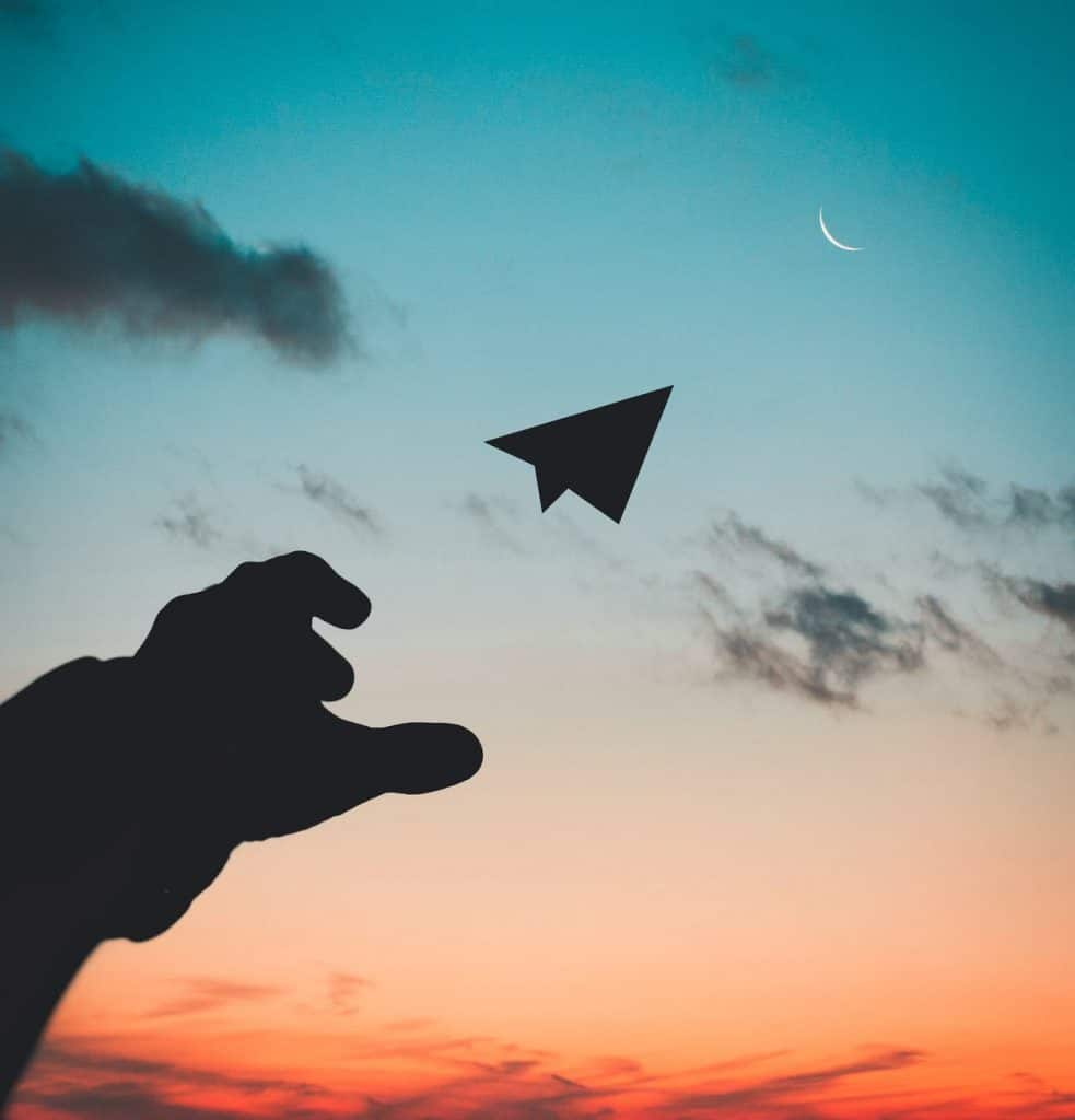 A paper plane being thrown into the sunset