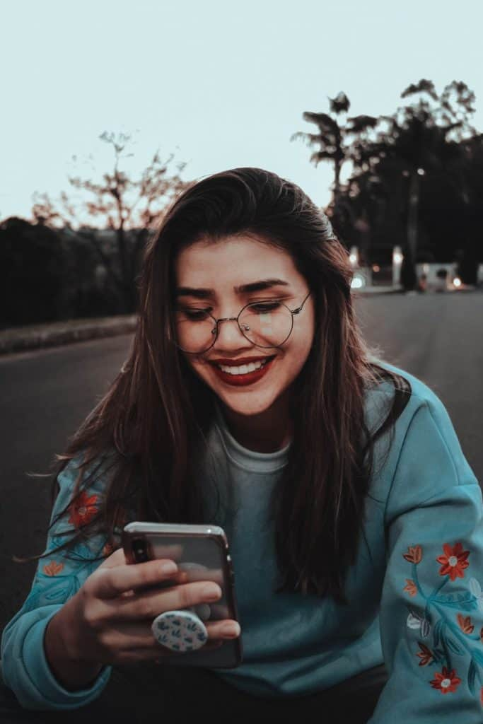 A girl smiling at her phone