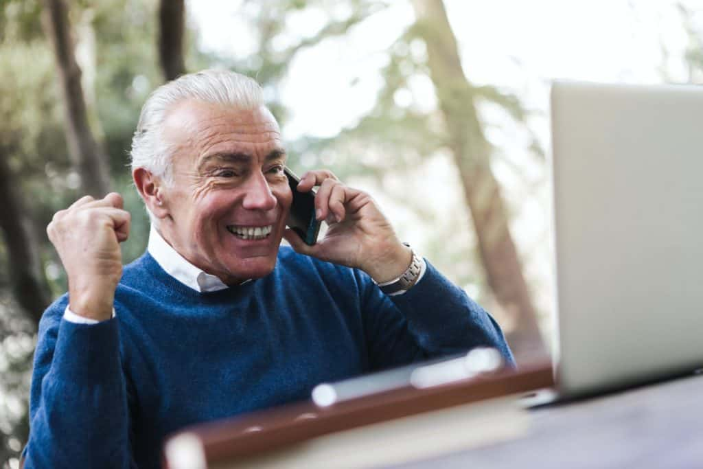An elderly man smiling as he makes a phone call