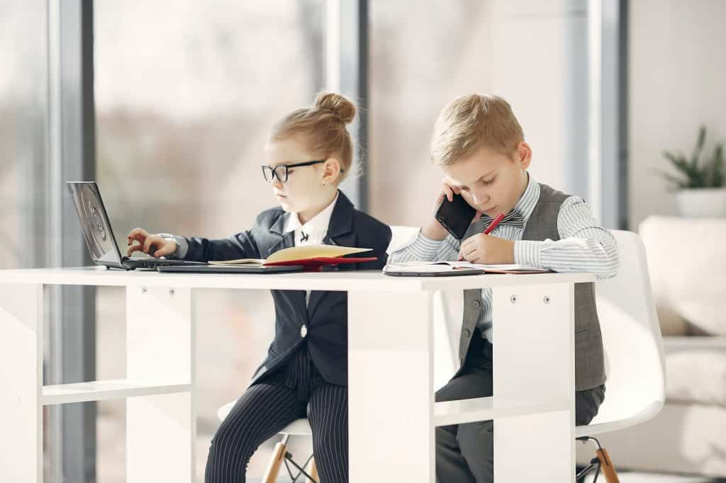 Two young children on the phone dressed as businessmen