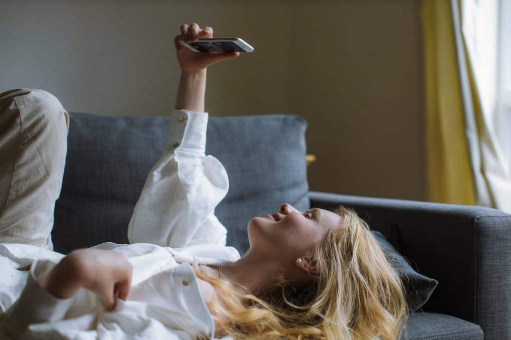 A girl lying on the sofa holding her phone up