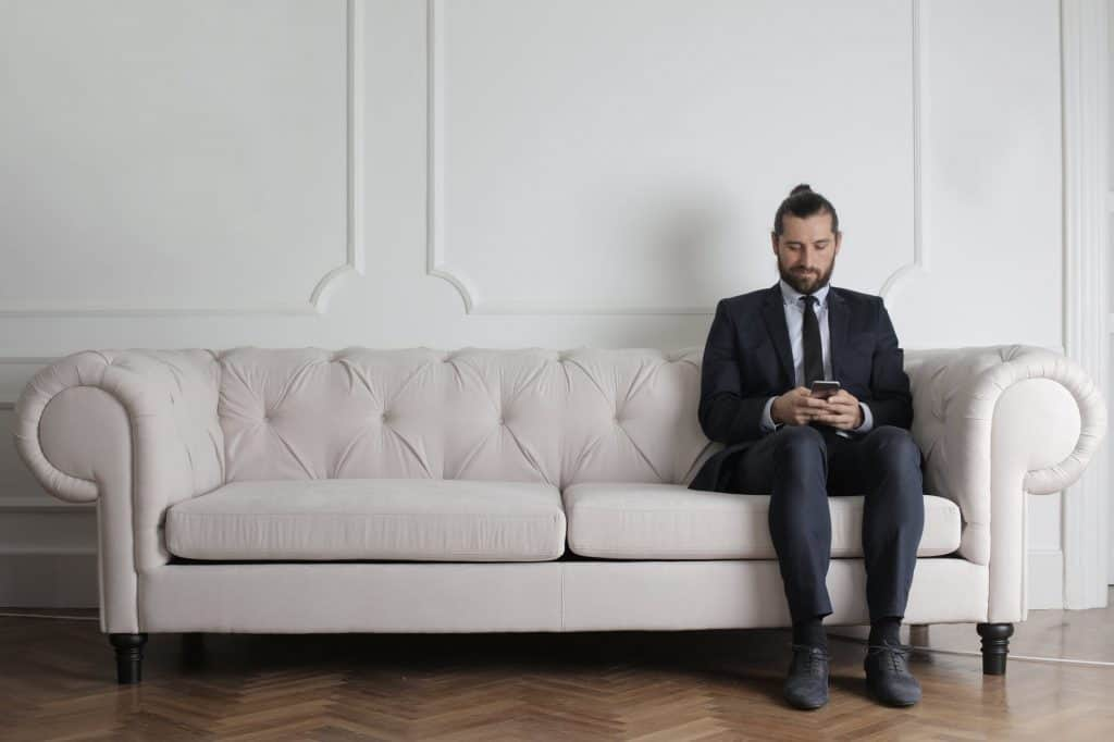 A businessman sitting on a white sofa