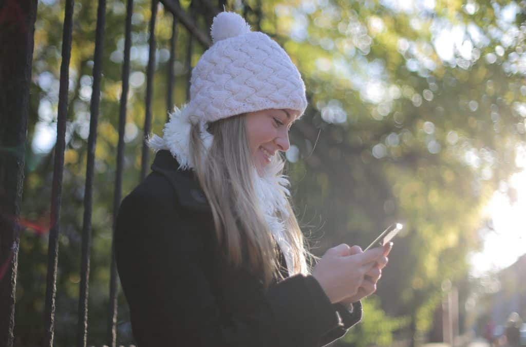 A woman in a white winter hat looking down at her phone
