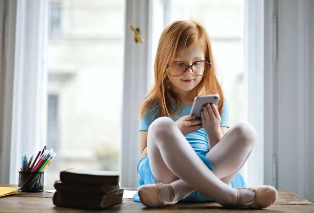 A little girl with red hair playing with her phone