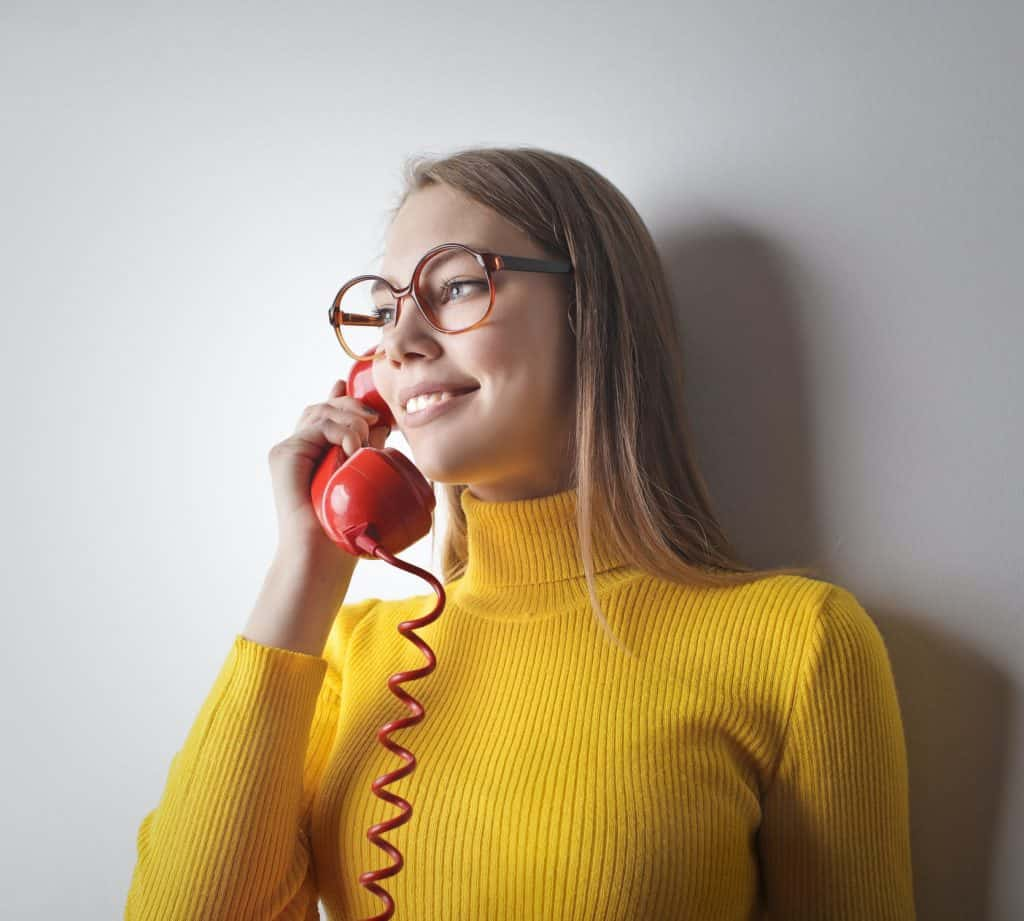 A woman in a yellow sweater holding a red phone