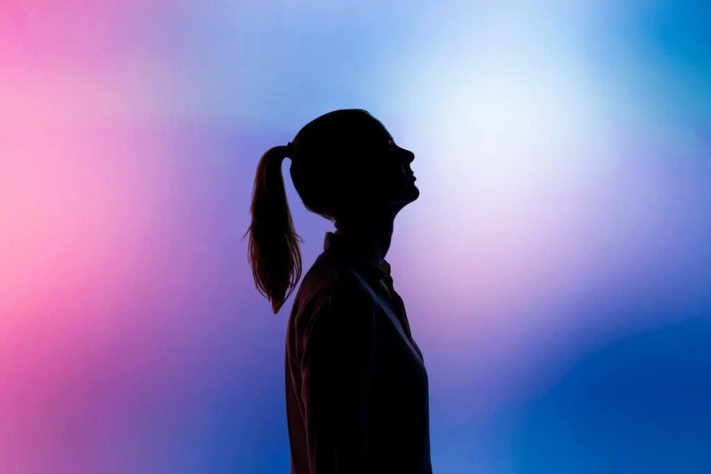 A silhouette of a woman on a pink and purple background
