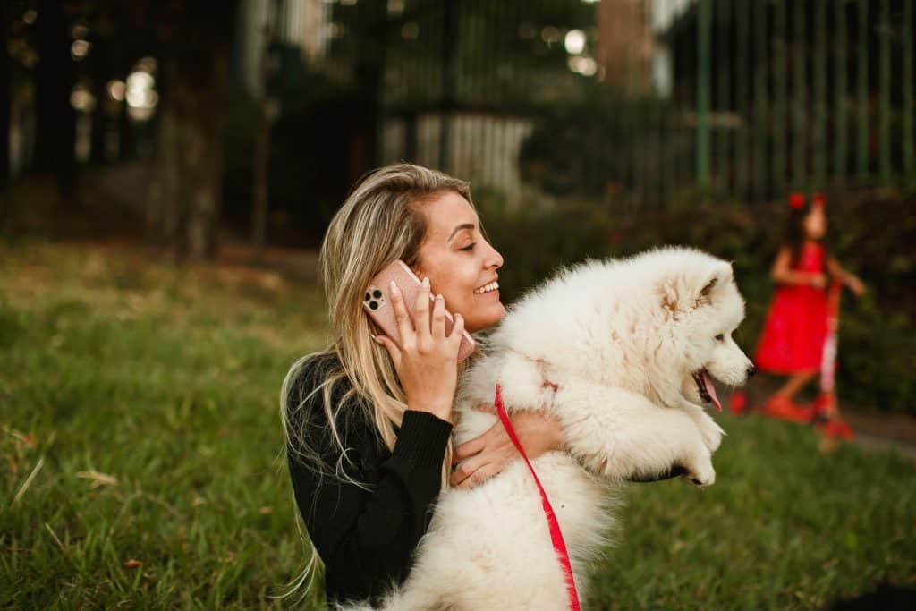 A woman holding a white dog as she talks on the phone