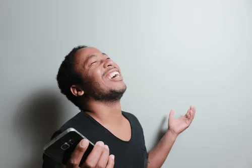 A man laughing as he holds his phone