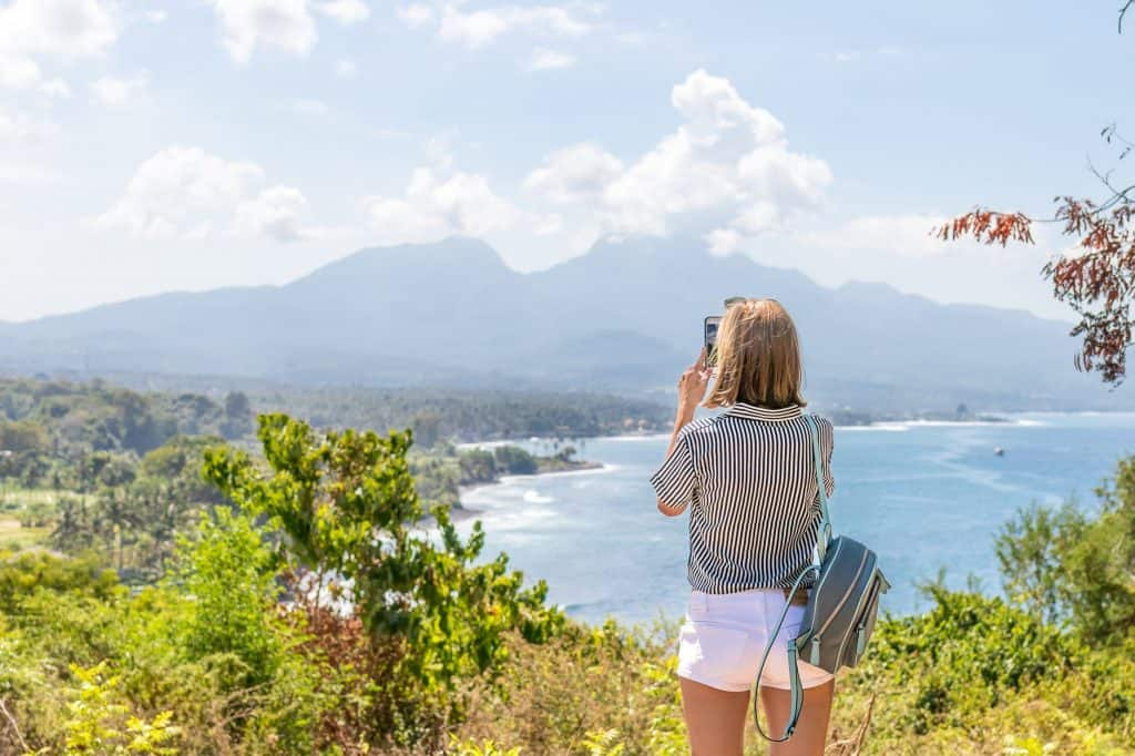 A girl standing over a lake and taking a picture