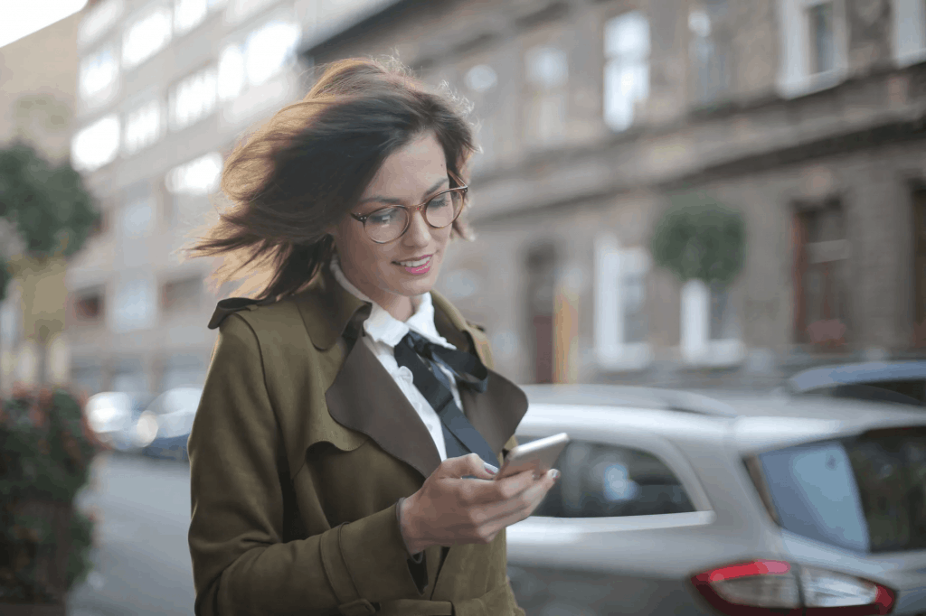 A woman wearing a coat and holding her phone