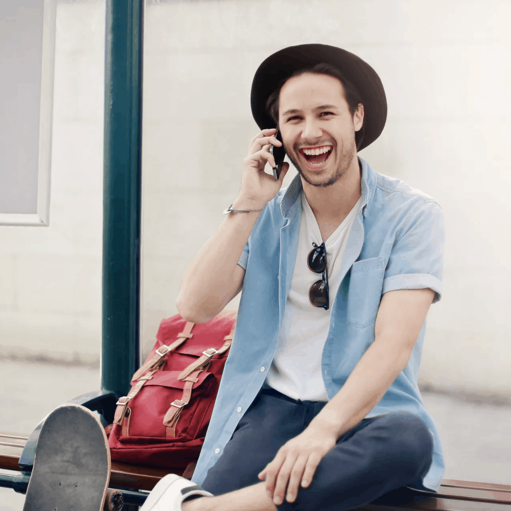 A trendy man smiling as he speaks on the phone