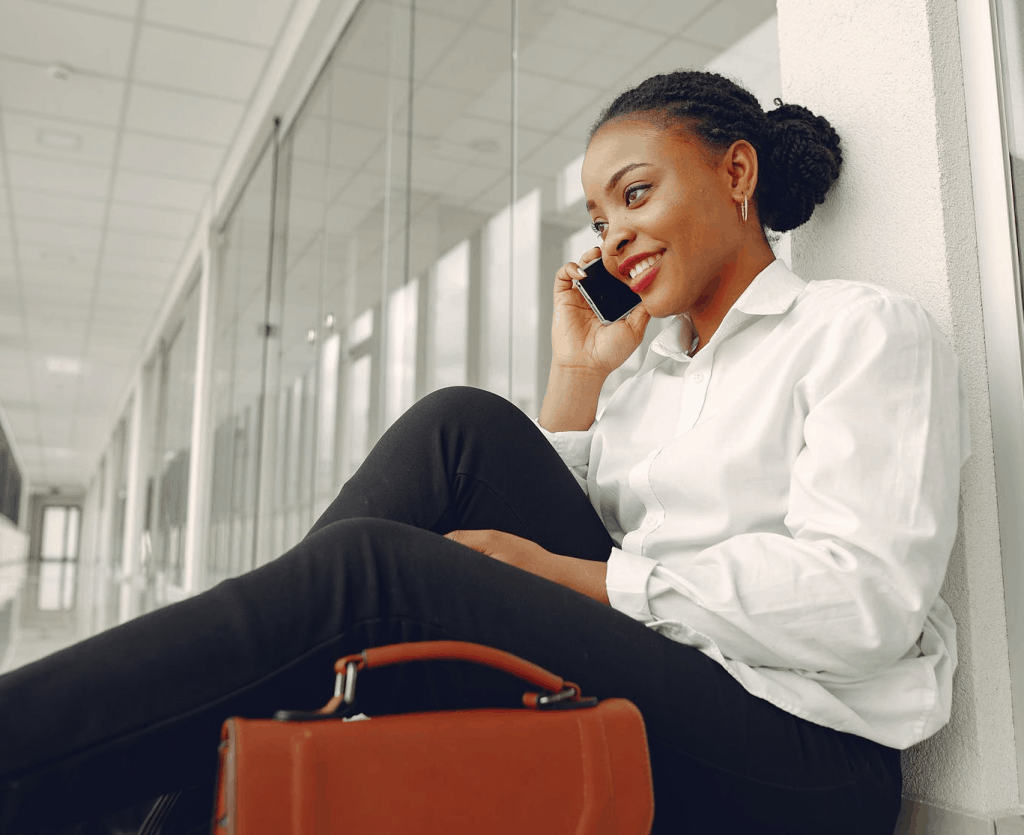 A woman sitting on the floor of a modern office speaking on the phone