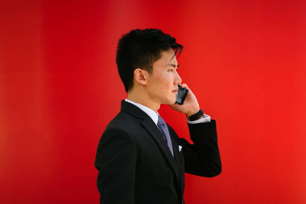 An Asian man in a suit talking on the phone in front of a red background