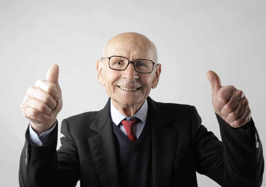 An elderly man dressed in a suit with his thumbs up