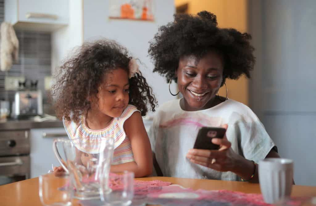 A mother and daughter holding a cellphone