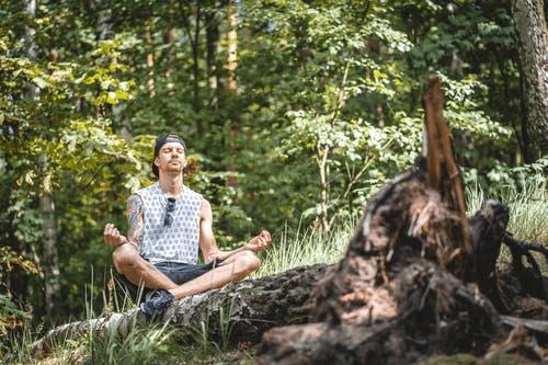 A man meditating next to a tree log