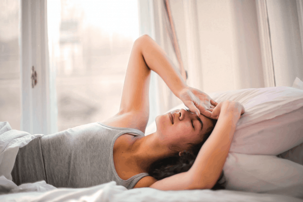 A woman laying in bed with her hands over her head