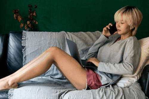 An Asian girl sitting on the couch on her phone