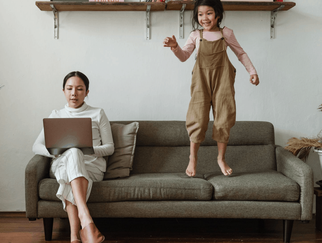 A mother working on the sofa with her daughter jumping next to her