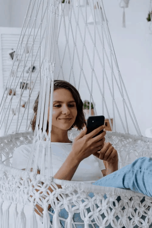 A woman smiling in a hammock with her phone