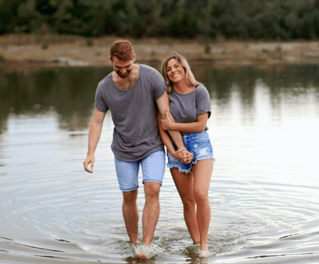 A happy couple standing together in a lake