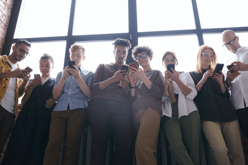 A group of people standing by the window holding their phones