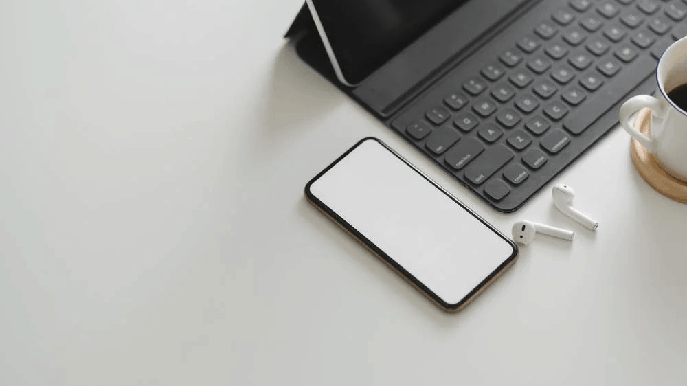 A blank phone screen next to a laptop