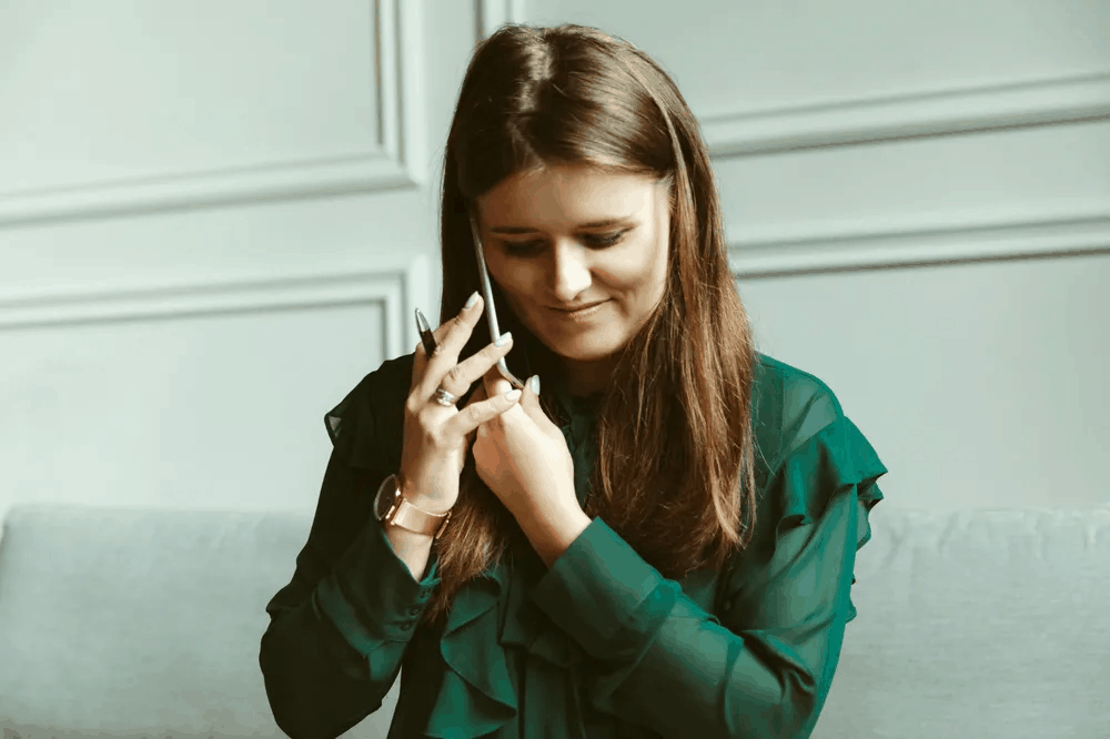 A young woman in an olive green shirt speaking on the phone