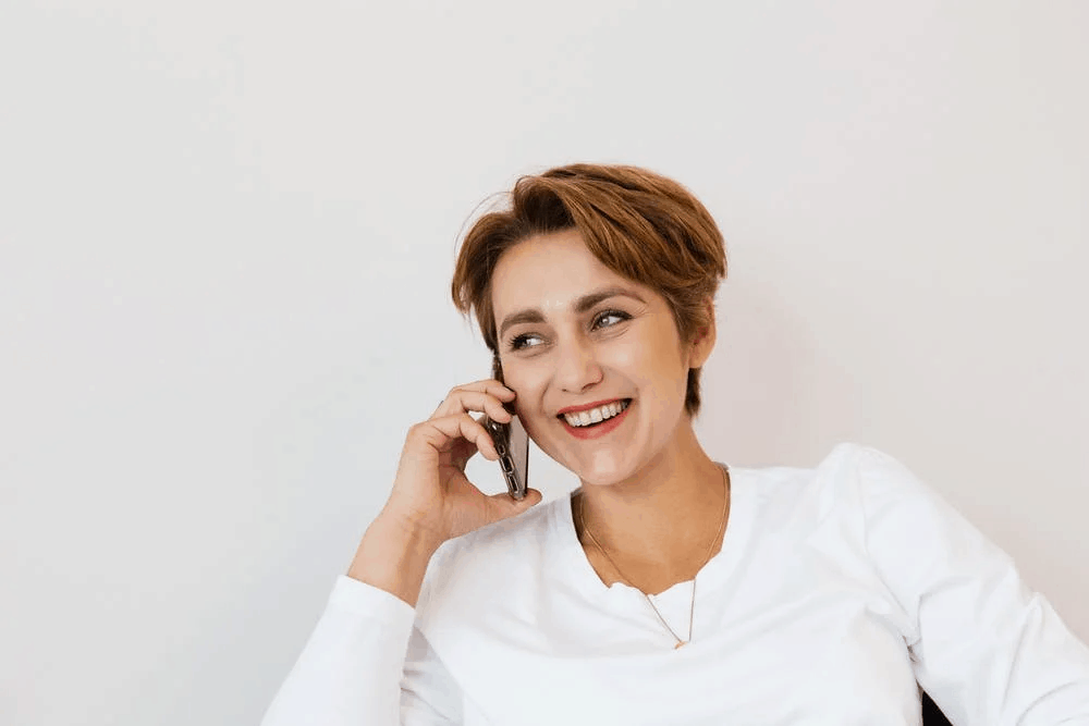 A happy woman with short hair speaking on the phone