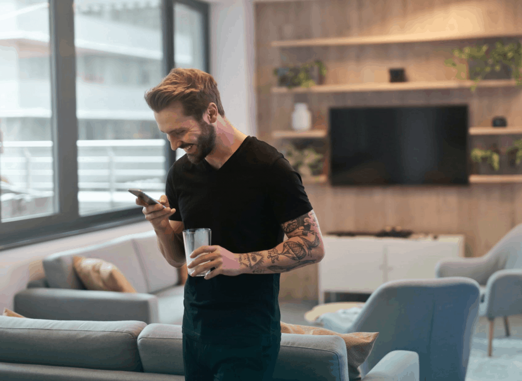 A man in a black t-shirt holding his phone