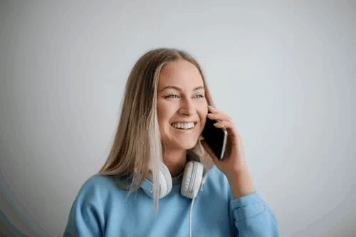 A blonde woman in a blue sweater speaking on the phone