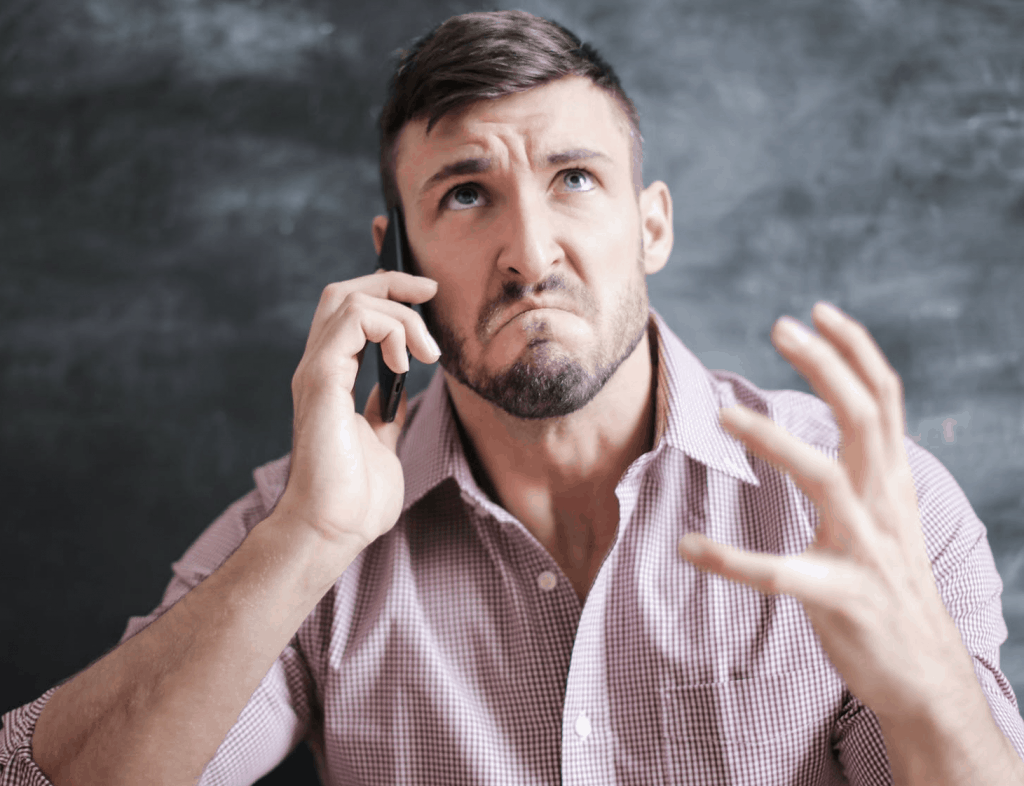 A man in a pink dress shirt angry on the phone