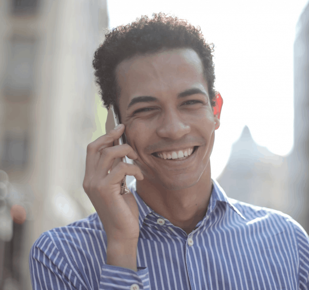 A man in a stripped dress shirt smiling on the phone