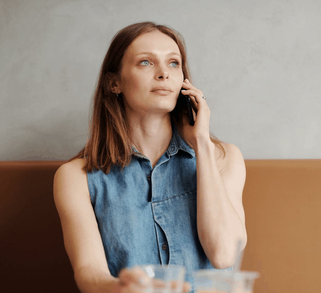 A woman in a denim shirt speaking on the phone