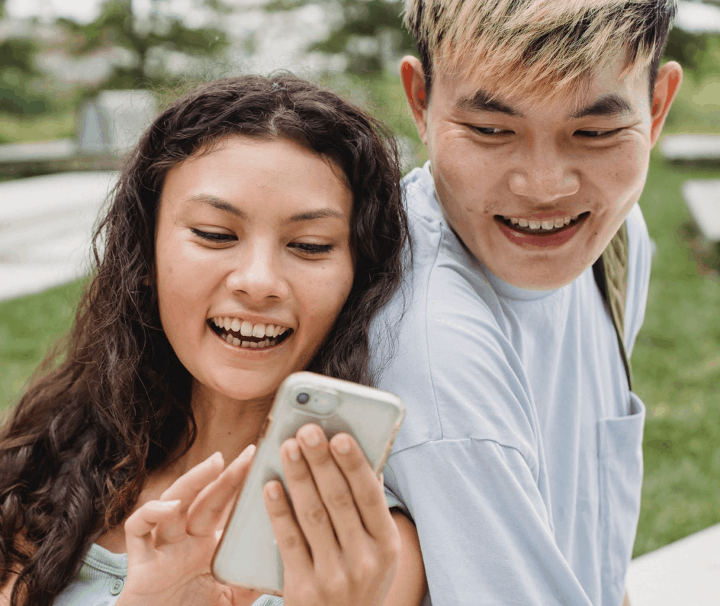 An Asian couple smiling while looking at a phone screen