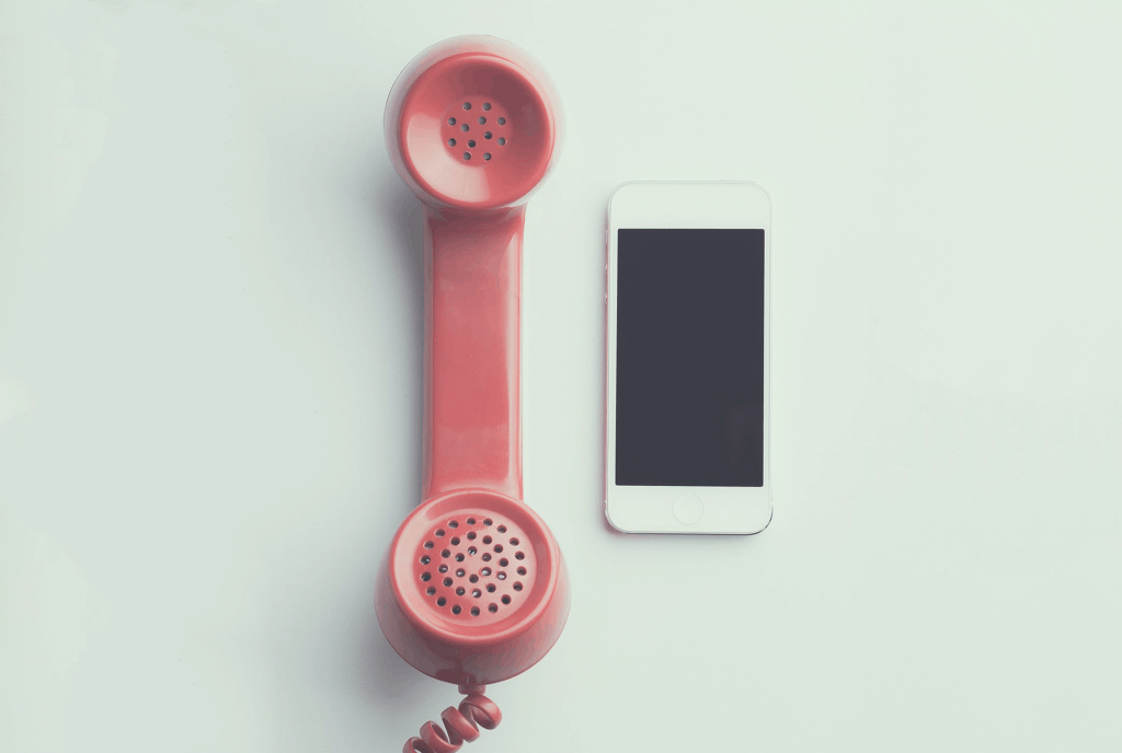 A red home phone next to a white mobile phone