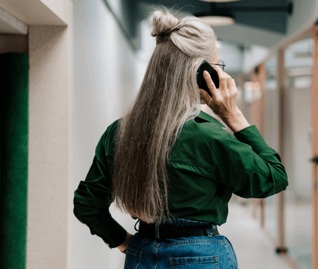 The back of a woman with long gray hair speaking on the phone