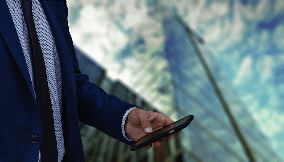 A buisnessman holding a phone in front of a tall building