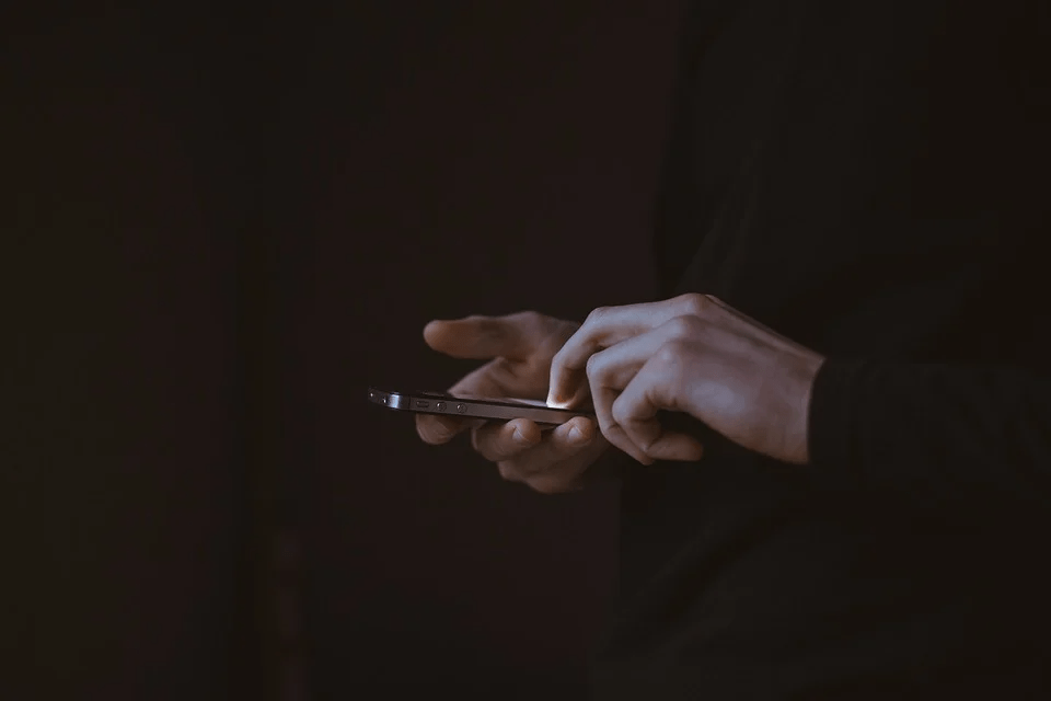 A man holding a phone on a black background
