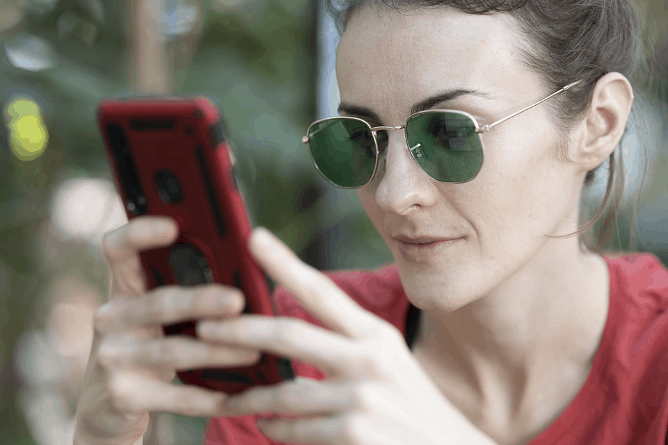 A woman wearing sunglasses holding a smartphone