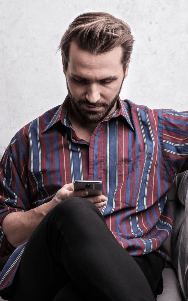 A man in a stripped shirt looking at his phone