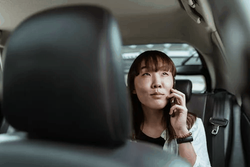An Asian woman speaking on the phone while sitting in the car