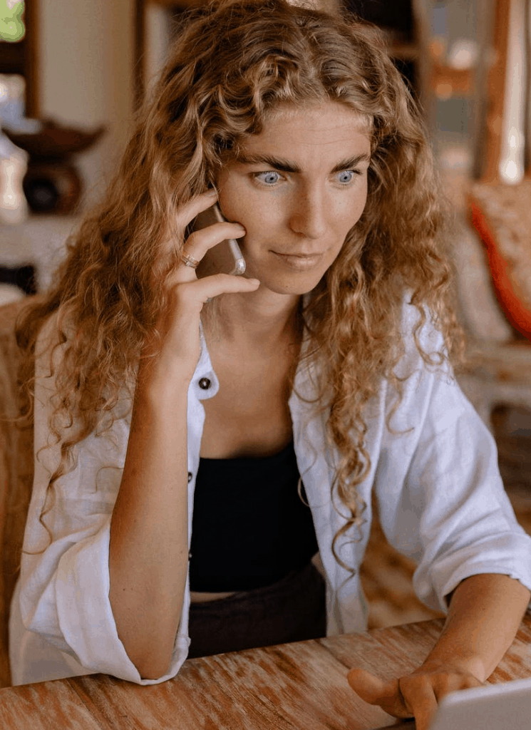 A blonde curly hair woman looking shocked on the phone