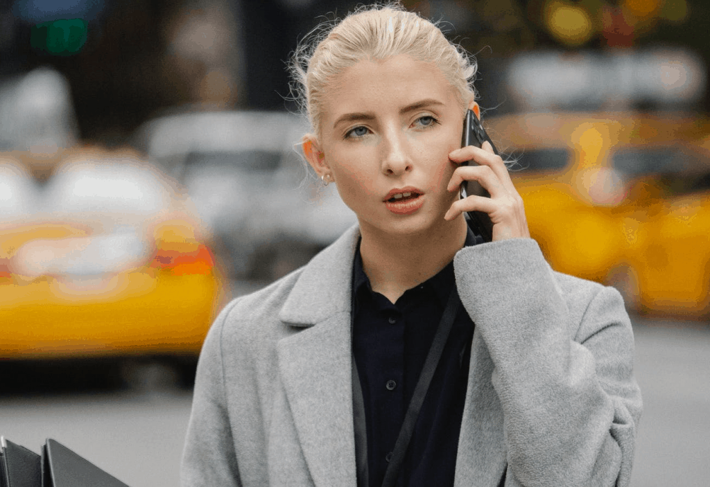 A blonde woman speaking on the phone