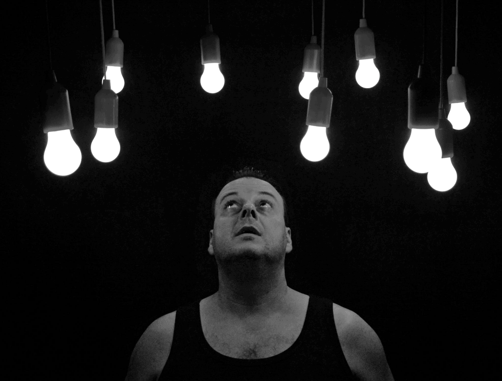 A man in a black tank top looking up at light bulbs